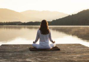 Woman meditating by lake.